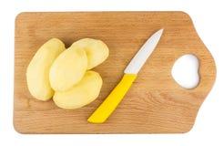 Слезли сырцовые картошки и керамический нож на hardboard Стоковая Фотография RF