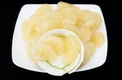 Слезли сладостный зеленый грейпфрут на белом блюде против черноты назад Стоковые Изображения