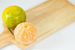 Слезли tangerines на деревянной плите на белой предпосылке с космосом экземпляра Стоковое Фото