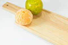 Слезли tangerines на деревянной плите на белой предпосылке с космосом экземпляра Стоковые Изображения