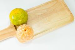 Слезли tangerines на деревянной плите на белой предпосылке с космосом экземпляра Стоковые Фото