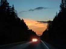 Слепимость фар автомобиля в движении вечера Стоковое фото RF