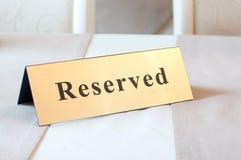 Сдержанно знак, ресервирование На таблице Цвет золота стоковые изображения