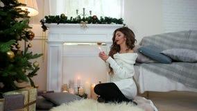 Сделайте желания, девушку с свечой в его руке, сидя на камине и рождественская елка, думает желания ` s Нового Года акции видеоматериалы