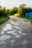 Сделайте ямки на дороге деревни с водой после дождя на заходе солнца Стоковые Изображения RF