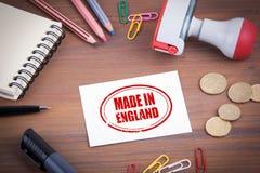Сделанный в штемпеле Англии Деревянный стол офиса с канцелярскими принадлежностями, деньгами стоковые фотографии rf