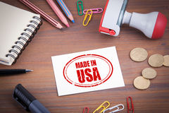 сделанный штемпель США Деревянный стол офиса с канцелярскими принадлежностями, деньгами и стоковое изображение