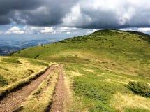 След гравия через горы с драматическими облаками Стоковые Фотографии RF