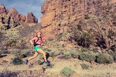 След женщины бежать в горах с рюкзаком Стоковое Изображение RF