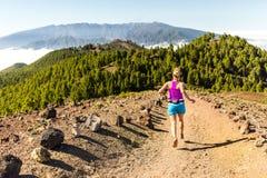 След молодой женщины бежать в горах на солнечный летний день стоковые изображения rf