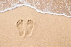 След ноги на пляже в предпосылке песка Стоковые Изображения