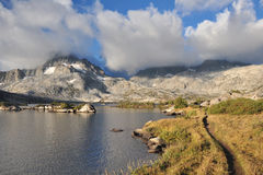 След облачного покрова озера высокая гор стоковые изображения