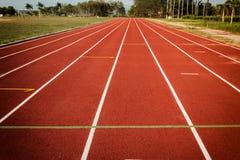 След спортсмена или идущий след, резиновые зерна красная предпосылка, Fo Стоковые Изображения RF