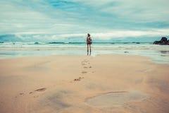 Следы ноги выведенные молодой женщиной на пляж стоковые изображения