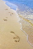 Следы ноги на пляже морем. Стоковое Фото