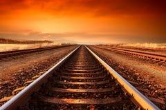 Следы поезда идут к горизонту в величественном заходе солнца Стоковые Изображения RF