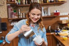 Сливк женщины Barista лить, который нужно придать форму чашки на кофейне стоковое фото