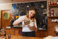 Сливк женщины Barista лить, который нужно придать форму чашки на кофейне стоковые фото