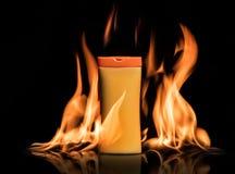 Сливк предохранения от Солнця, лосьон стоит в огне на черной предпосылке Стоковое фото RF