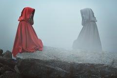 С капюшоном женщина и ее темное отражение Стоковая Фотография