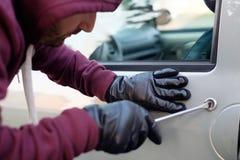 С капюшоном похититель пробуя раскрыть автомобиль Стоковое фото RF