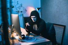 с капюшоном хакер в маске считая украденные деньги стоковые изображения rf
