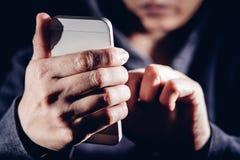С капюшоном хакер злодеяния кибер используя интернет мобильного телефона рубя внутри стоковое изображение rf