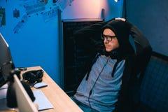 с капюшоном хакер ослабляя на стуле перед стоковое изображение