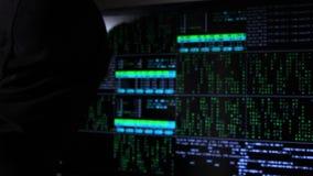 С капюшоном человек как хакер работает с цифровыми данными на мониторе и внезапно поворачивает вокруг Сторона предусматривана с м видеоматериал