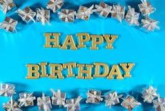 С днем рождения золотые подарки текста и серебра на сини стоковое фото rf