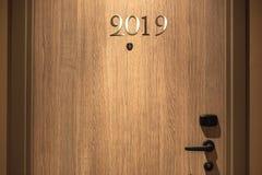 С Новым Годом! концепция 2019, помечая буквами на двери гостиницы стоковое изображение rf