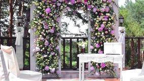 Сдобрите для свадебной церемонии, украшенный с розовыми цветками пионов и растительность, в сосновом лесе на террасе видеоматериал