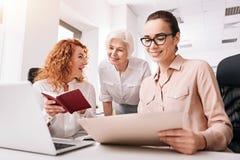 Словоохотливые коллеги деля идеи в офисе Стоковое Фото