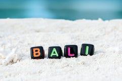 Слово Бали сделано пестротканых писем на снег-белом песке против голубого моря Стоковое Фото