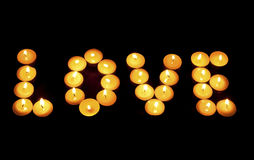 Слово ВЛЮБЛЕННОСТЬ положено вне от горящих свечей стоковая фотография