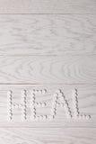 Слово излечивает сделанный пилюлек на таблице Стоковое фото RF
