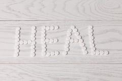 Слово излечивает сделанный пилюлек на таблице Стоковые Фотографии RF