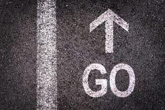 Слово идет и стрелка написанная на дороге асфальта Стоковая Фотография RF