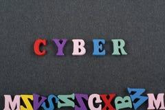 Слово КИБЕР на черной предпосылке составленной от писем красочного блока алфавита abc деревянных, космосе доски экземпляра для те Стоковая Фотография RF