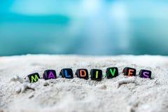 Слово Мальдивы сделано пестротканых писем на снег-белом песке против голубого моря Стоковое фото RF