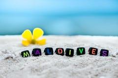 Слово Мальдивы сделано пестротканых писем на снег-белом песке против голубого моря Стоковые Изображения