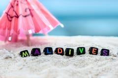Слово Мальдивы сделано пестротканых писем на снег-белом песке против голубого моря Стоковая Фотография