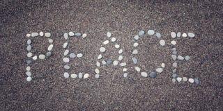 Слово 'мира' на песке Написанный с камешками постаретое фото Стоковое Фото