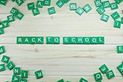 Слово назад к школе на деревянной предпосылке стоковые изображения