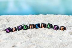 Слово Сейшельские островы сделано пестротканых писем на снег-белом песке против голубого моря Стоковые Изображения