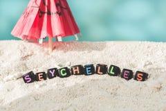 Слово Сейшельские островы сделано пестротканых писем на снег-белом песке против голубого моря Стоковая Фотография