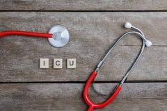 Слово текста ICU сделанное с деревянными блоками и красным сердцем, стетоскопом дальше Стоковое фото RF