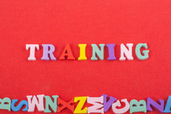 Слово ТРЕНИРОВКИ на красной предпосылке составленной от писем красочного блока алфавита abc деревянных, космосе экземпляра для те Стоковое Изображение RF
