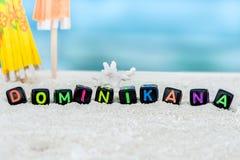 Слово Dominikan сделано пестротканых писем на снег-белом песке против голубого моря Стоковая Фотография
