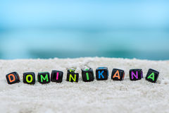 Слово Dominikan сделано пестротканых писем на снег-белом песке против голубого моря Стоковое Изображение